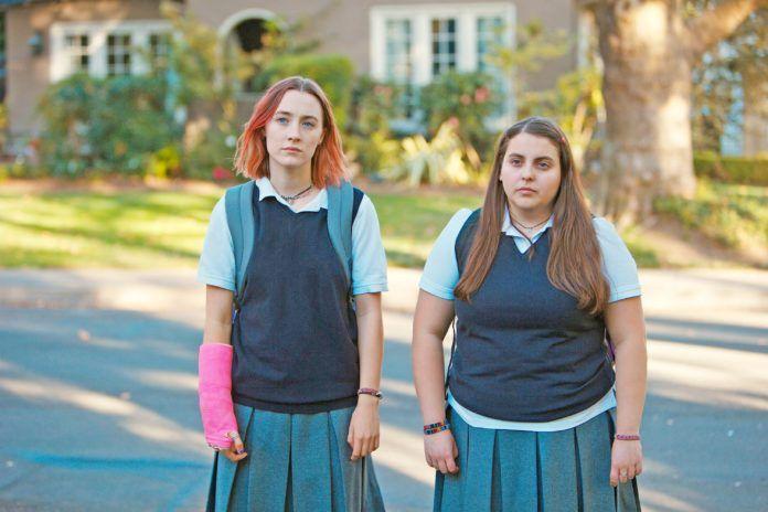 Dwie, stojące na ulicy dziewczynki w szkolnych uniformach. Dziewczyna z lewej ma różowy gips i czerwone włosy.