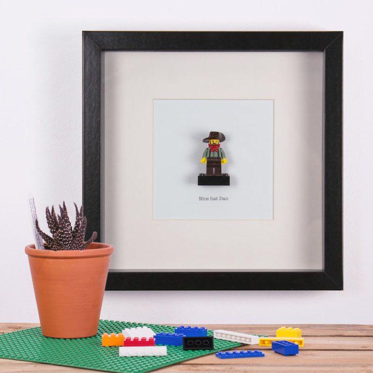 ludzik lego oprawiony w czarna ramke, ramka wisi na scianie, opok stoi na polce kwiatek