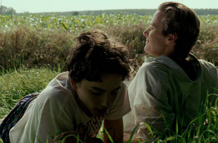 Mężczyzna i nastoletni chłopak leżą na polanie na włoskiej wsi