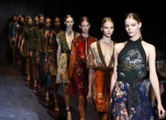 Szczupłe kobiety idące w rzędzie po wybiegu w różnokolorowych sukienkach.