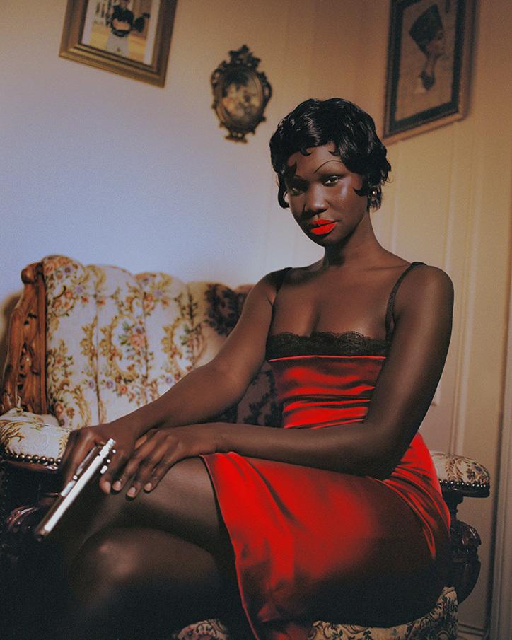 Czarnoskóra kobieta w czerwonej sukience z pistoletem
