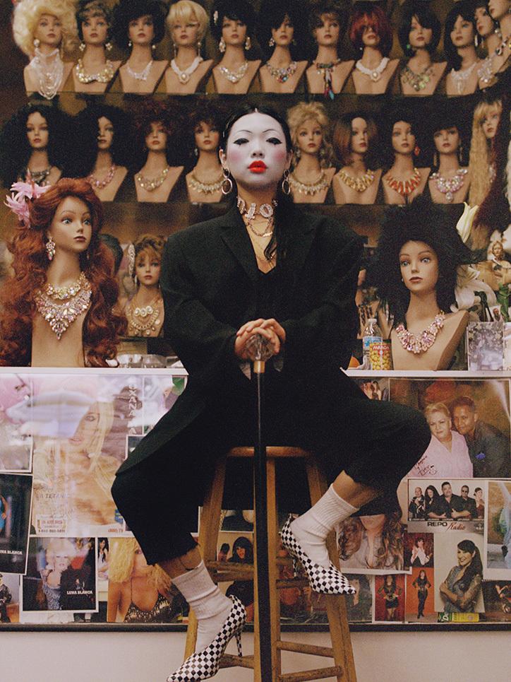 Kobieta z białą twarzą ubrana na czarno siedząca na stołku