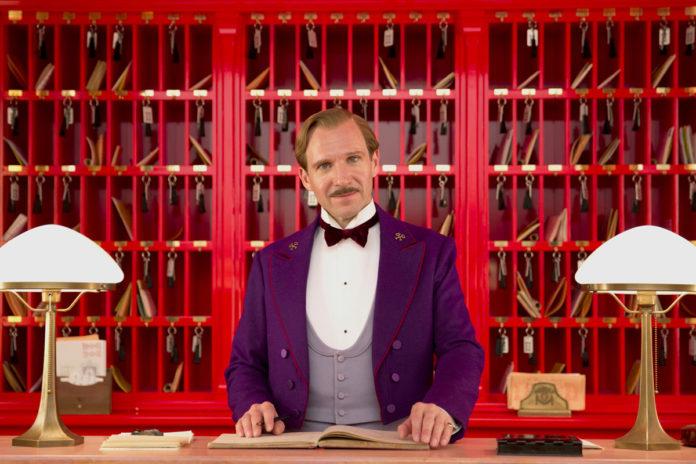 Mężczyzna stojący przy ladzie recepcji hotelowej