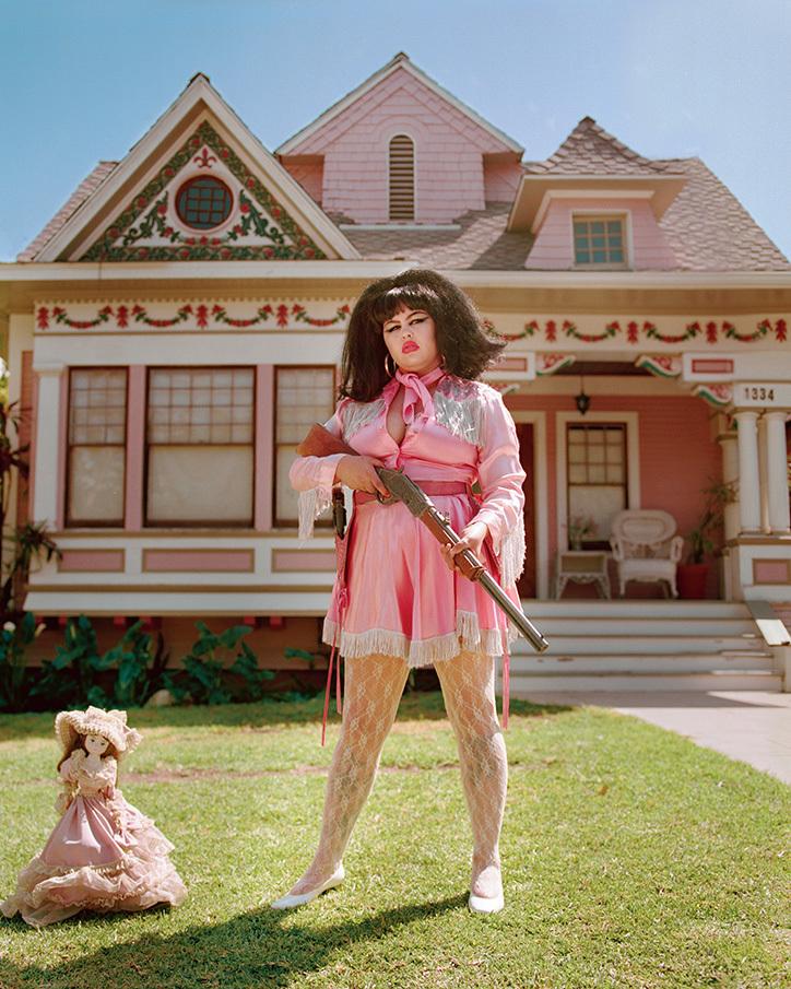Kobieta ubrana na różowo z karabinem w ręku