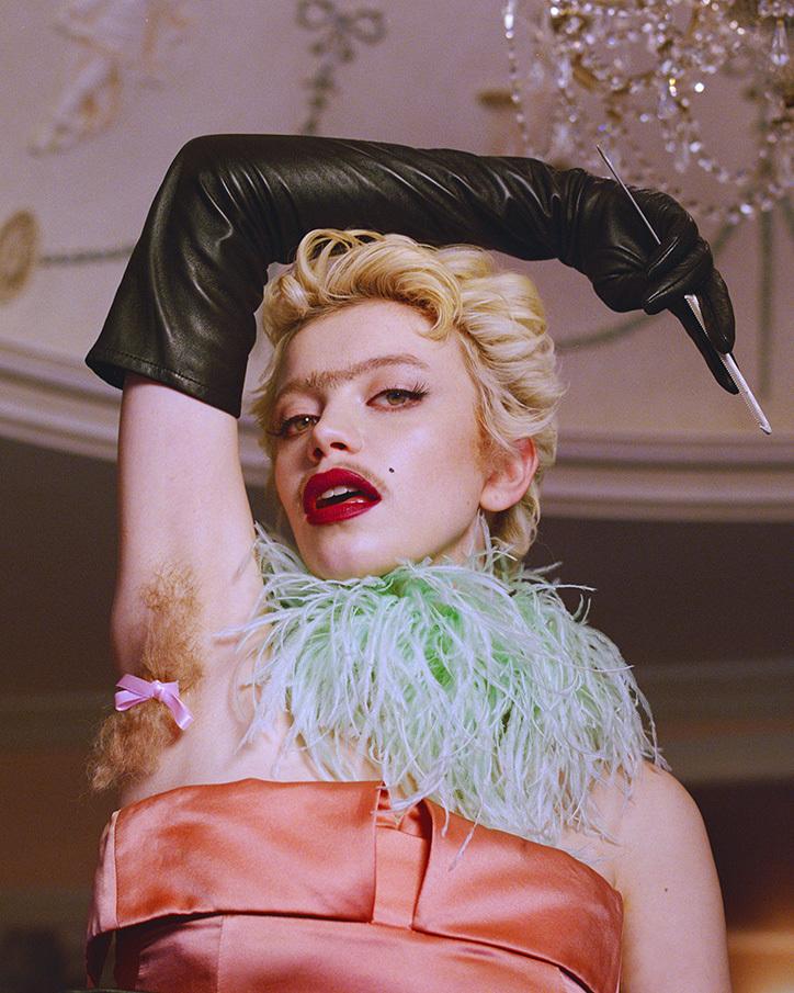 Kobieta w sukience i rękawiczkach z włosami pod pachą