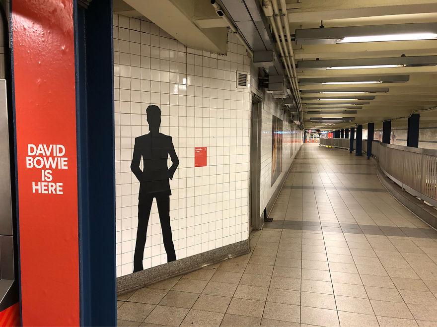 Cień Davida Bowiego na ścianie i napis BOWIE IS HERE