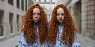 Dwie rudowłose bliźniaczki jednojajowe ubrane w takie same ubrania