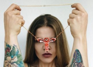 Kobieta trzymająca w dłoniach naszyjnik w kształcie macicy