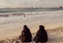 Dwie ubrane na czarno kobiety siedzące nad brzegiem morza