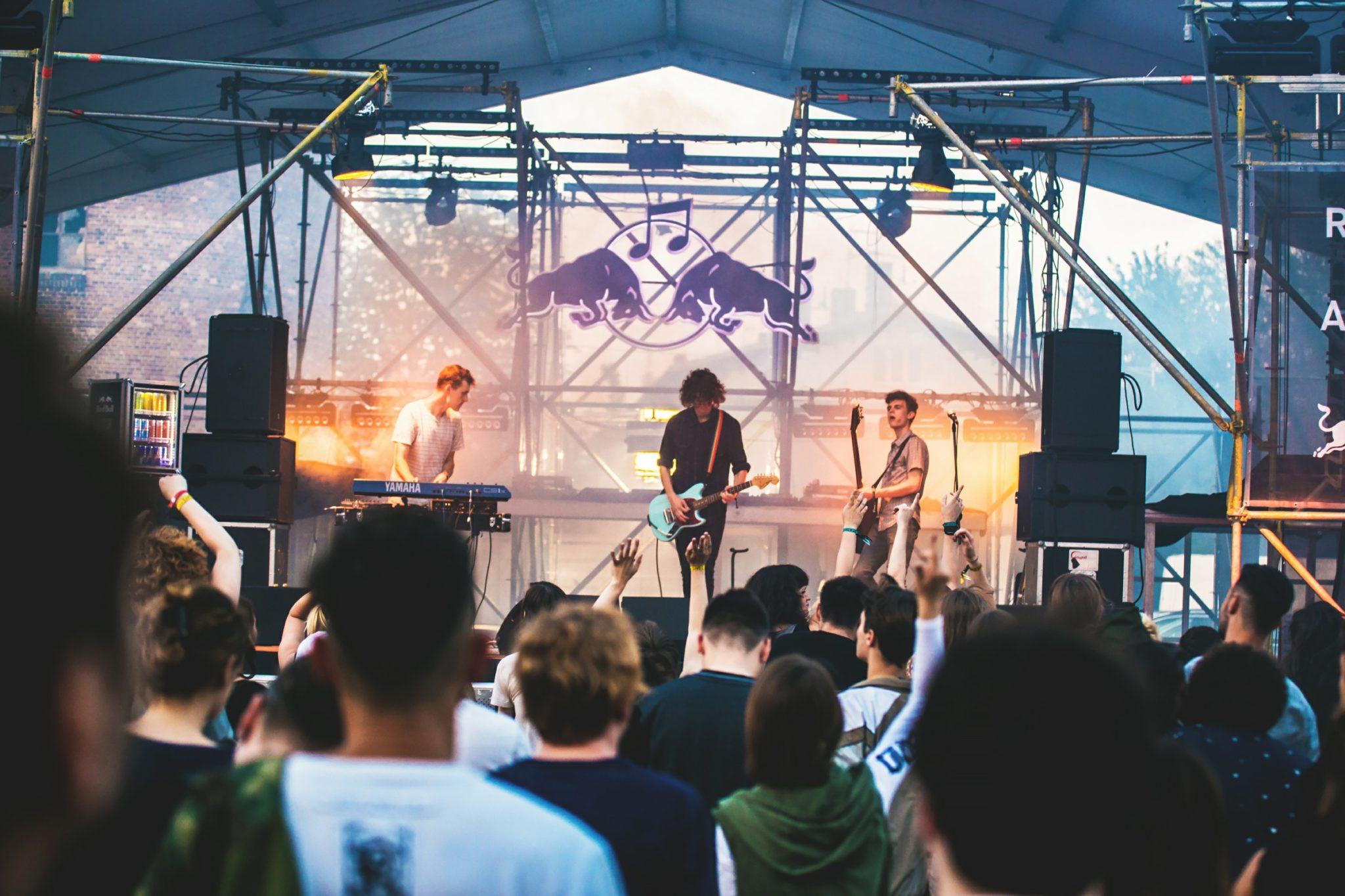 Koncert w plenerze na scenie trzech mlodych cchlopcow oraz publika tylem
