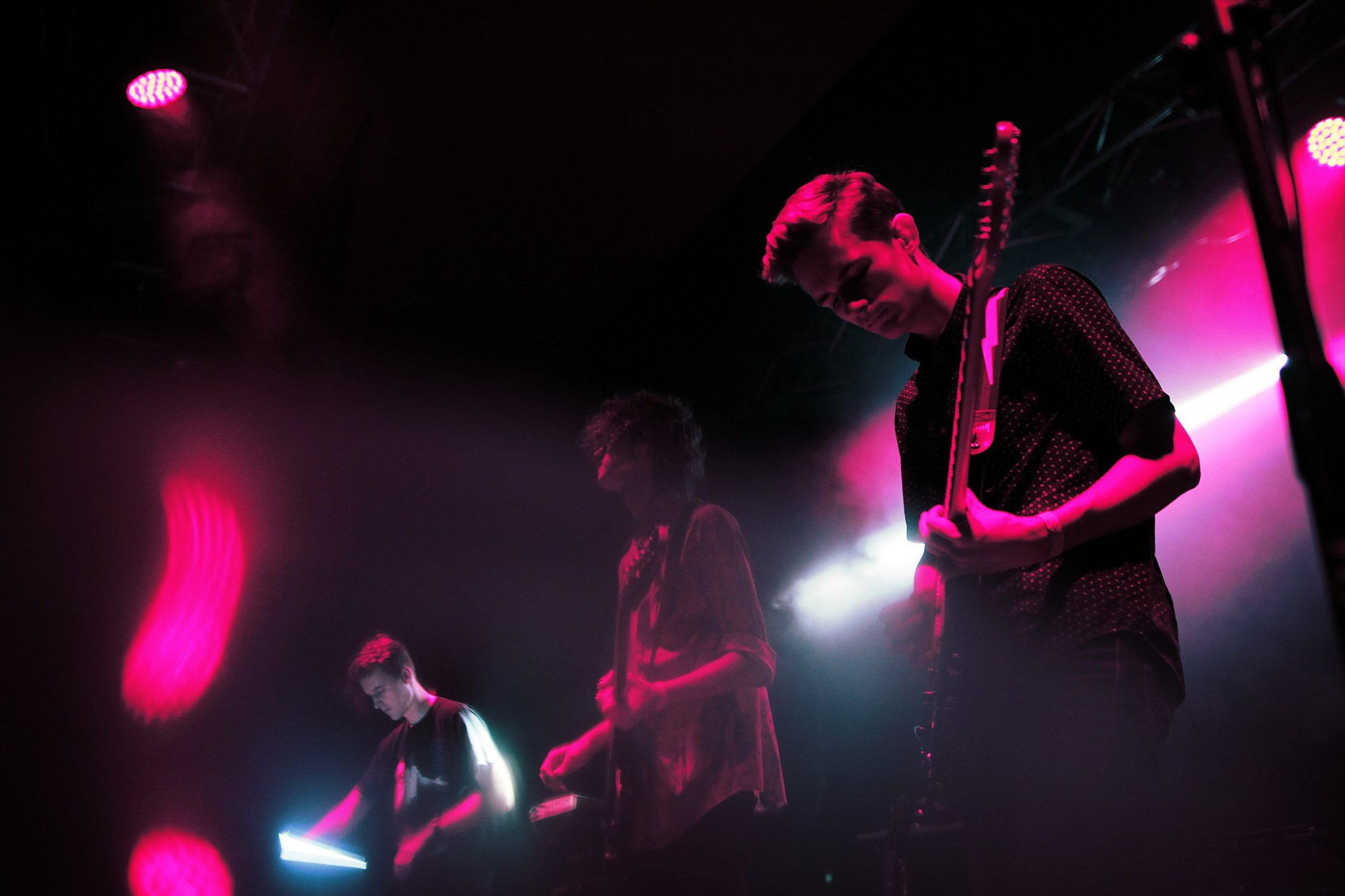 Trzech chlopcow na koncercie na scenie dwoch z gitara w rozowym swietle