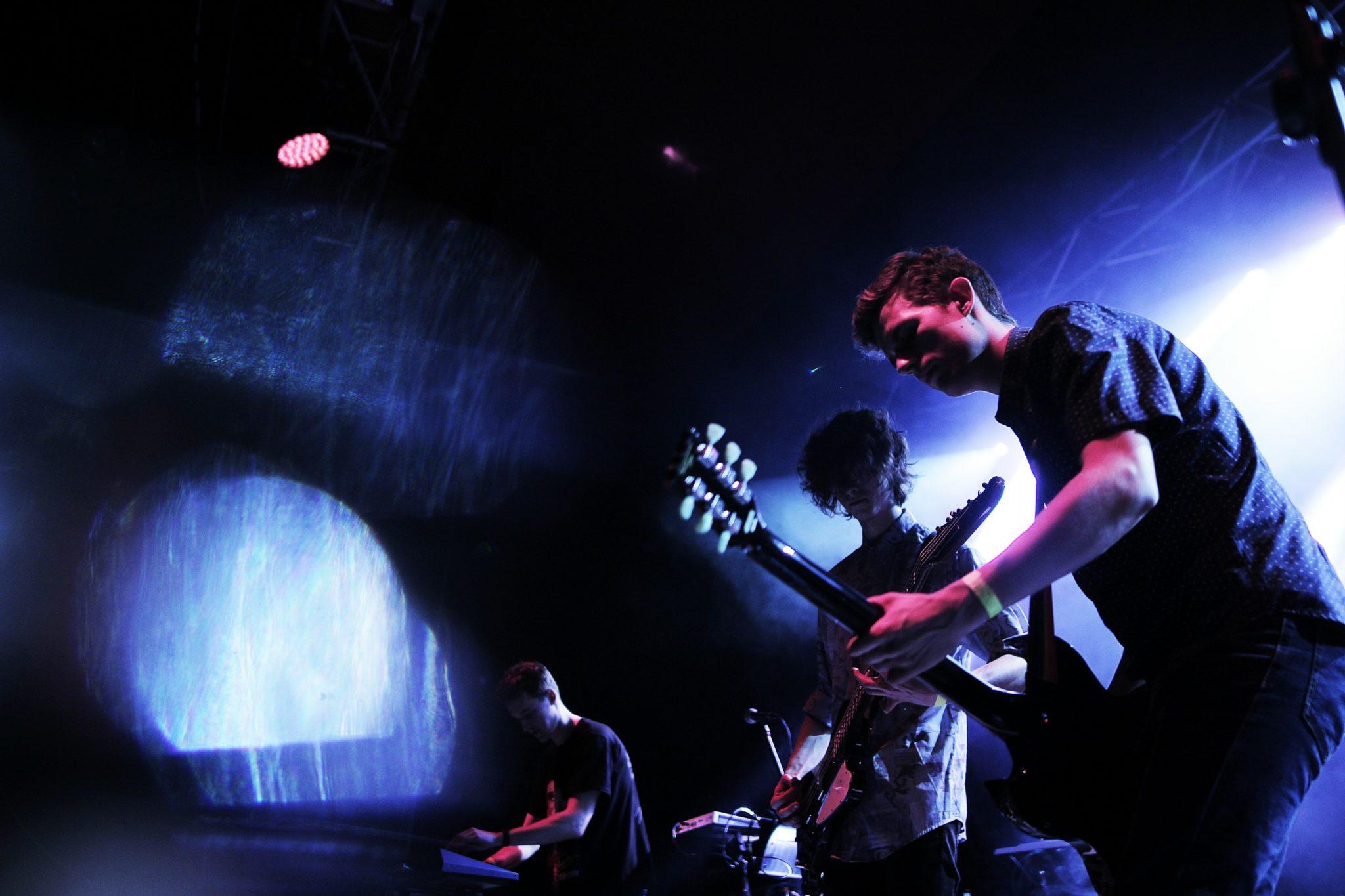 trzech chlopakow na koncercie w niebieskim swietle