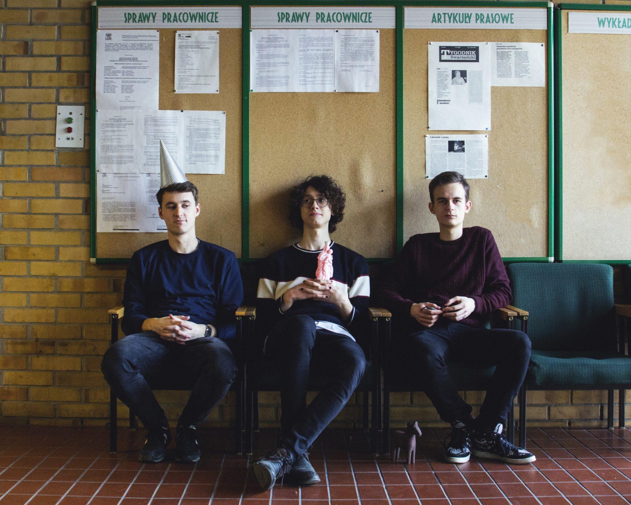 Trzech chlopakow w szkole siedza na tle tablicy ogloszen