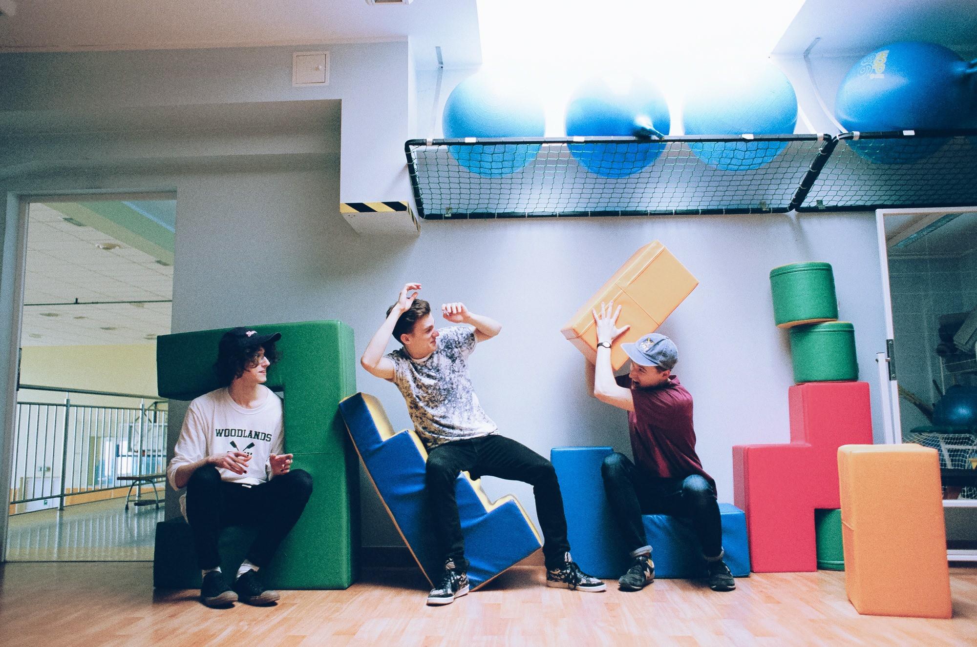 Trzech chłopakow w pokoju zabaw rzucaja sie kolorowymi kwadratami