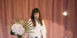 Na różowym tle stoi dziewczyna w brazowych dlugich wlosach za szklana lada a na ladzie stoi kwiat