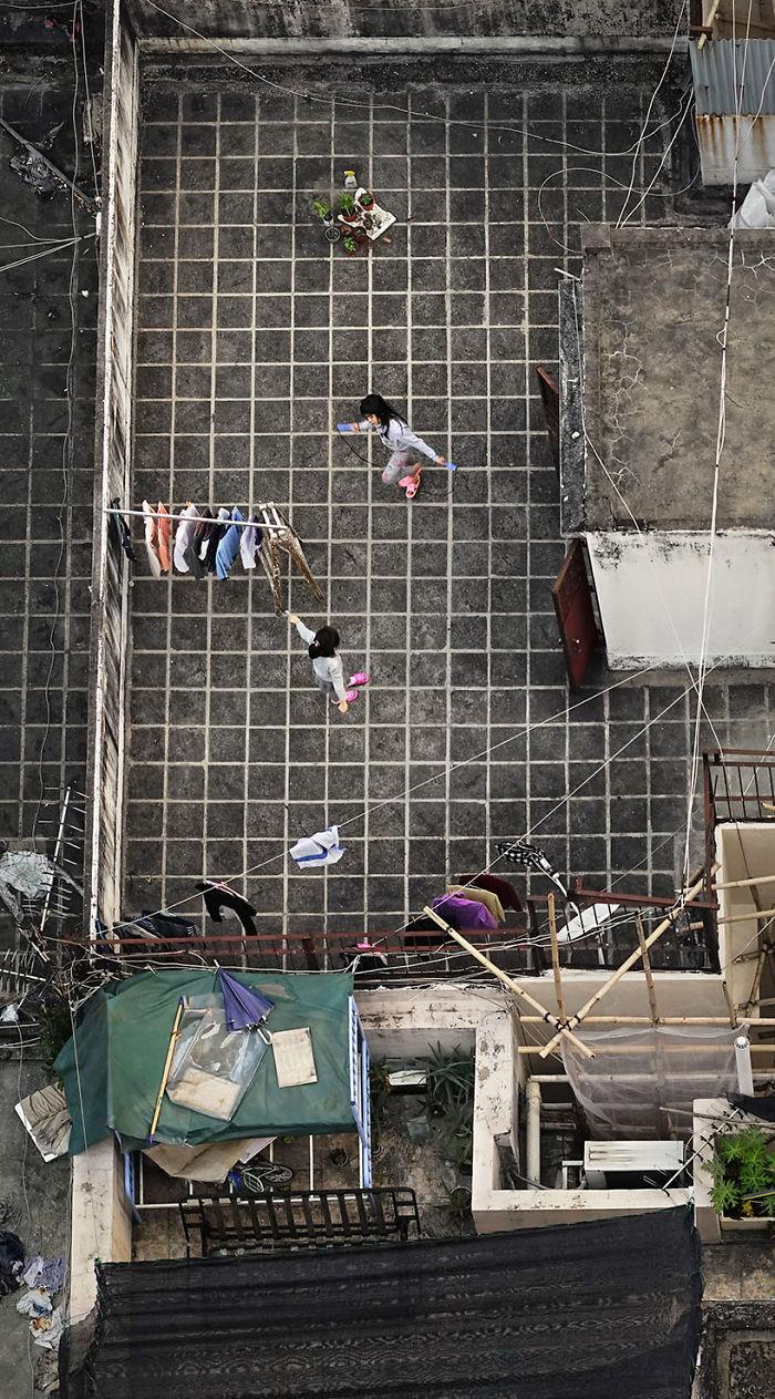 Widok dachu z lotu ptaka, kobieta wiesz pranie, dzieci się bawia