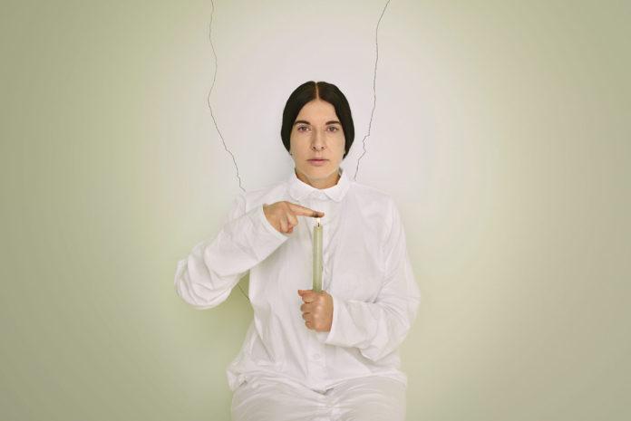 Kobieta w czarnych, związanych włosach w białym kombinezonie na tle białej ściany, trzyma w ręku białą, palącą się świecę, palec drugiej ręki przystawia do płomienia.