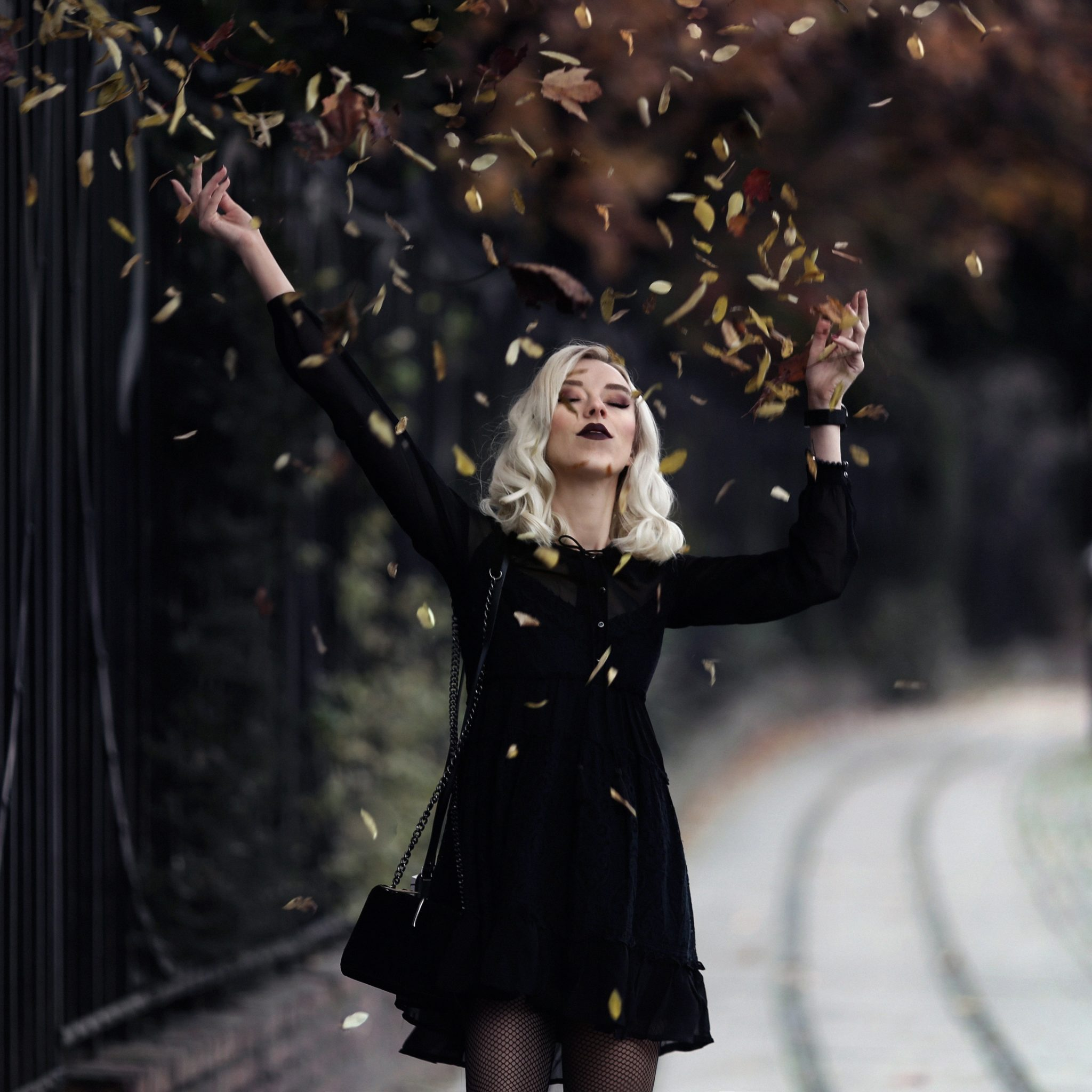 W parku stoi blondynka w czarnej sukience i podrzuca liscie do gory