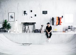 Mężczyzna w czarnym stroju siedzi obok psa w jasnym, minimalistycznym wnętrzu.