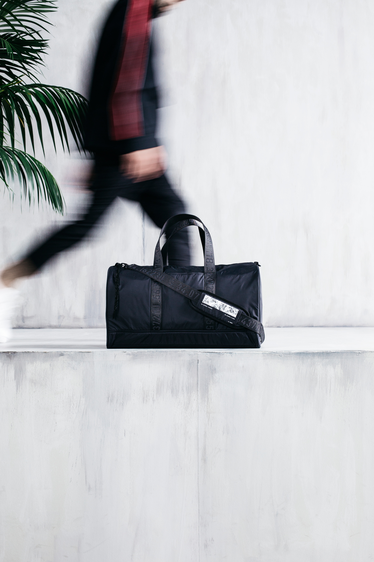 Czarna sportowa torba w betonowym wnętrzu, w tle palma i rozmazany idący człowiek.