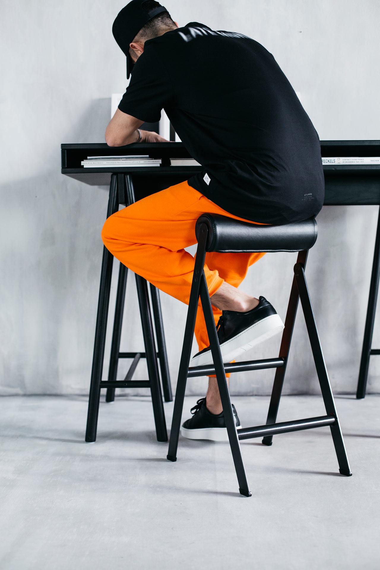 Mężczyzna w czarnej koszulce i pomarańczowych spodniach siedzi na czarnym stołku przy czarnym biurku.