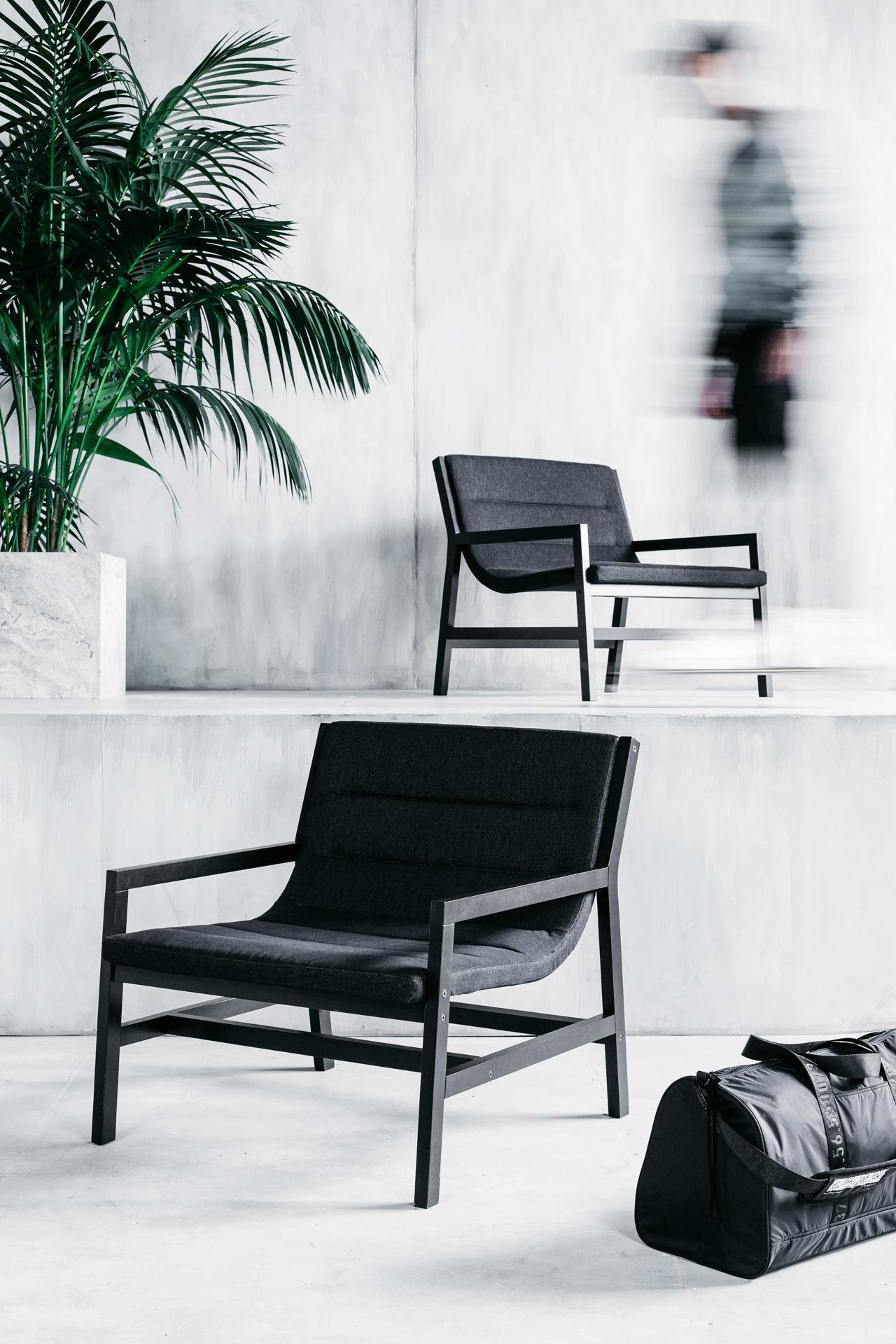 Czarne proste fotele w minimalistycznym betonowym wnętrzu.