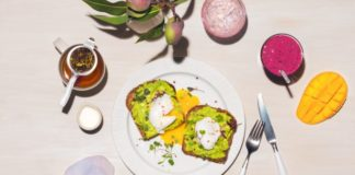 Na zdjęciu widać talerz z grzankami z awokado, koktale mleczne, mango oraz świeżo zaparzoną herbatę