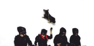 Czworo zamaskowanych, ubranych na czarno ludzi siedzących na podłodze