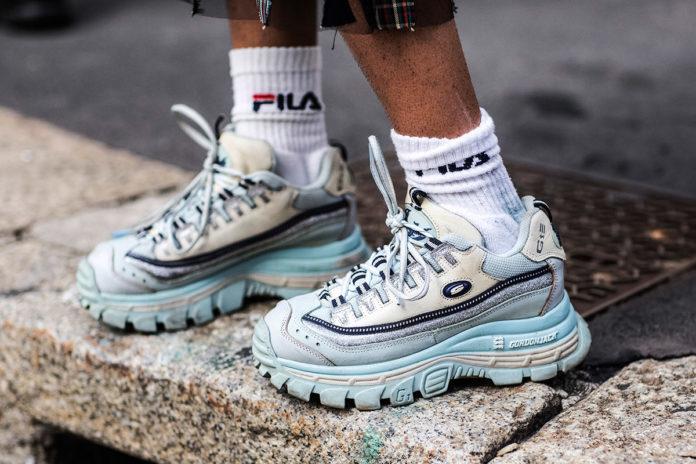 Zdjęcie męskich nóg w białych skarpetkach i szaro niebieskich, masywnych sneakersach.