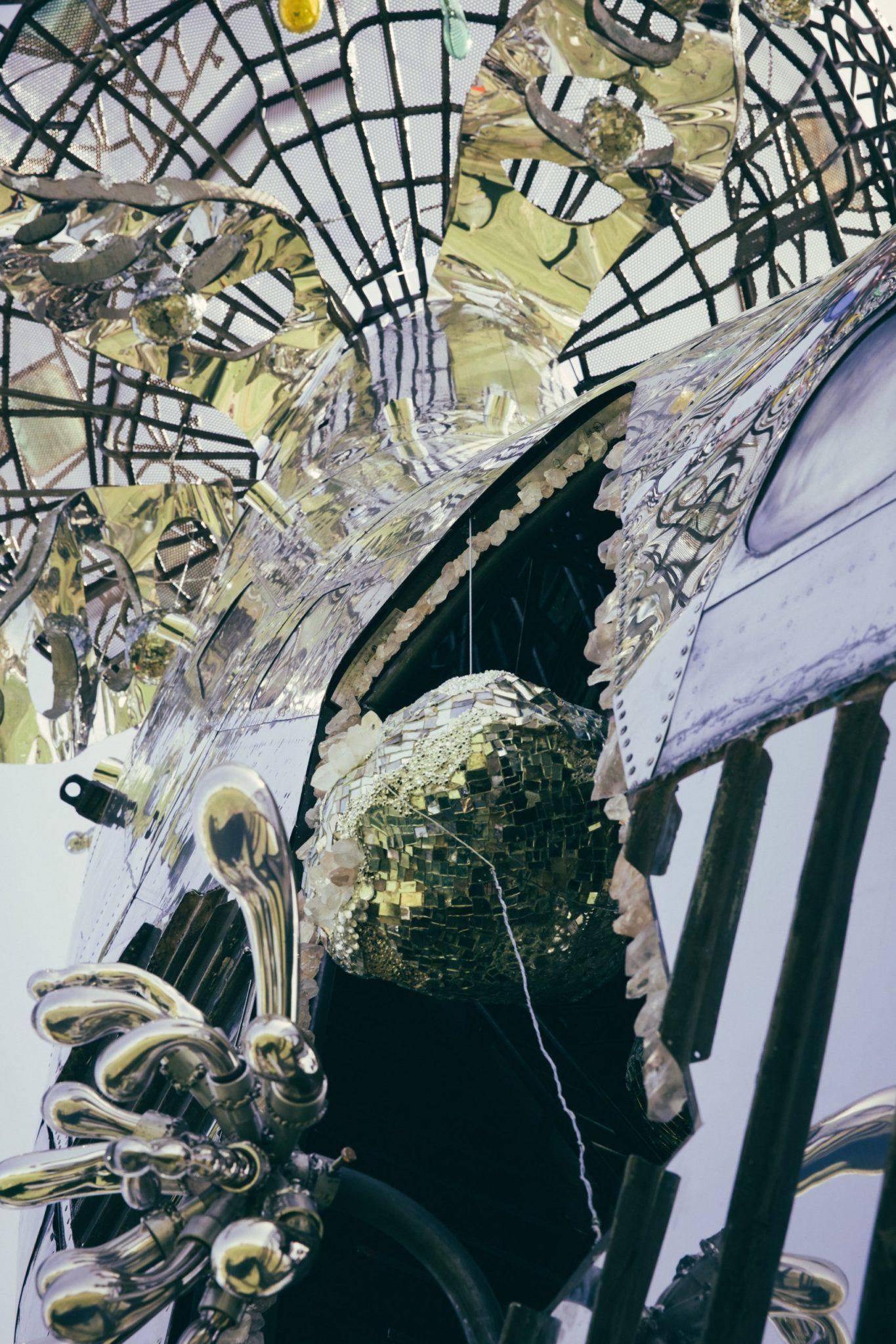 Błyszczący kadłub samolotu, kula dyskotekowa i szklana abstrakcyjna forma.