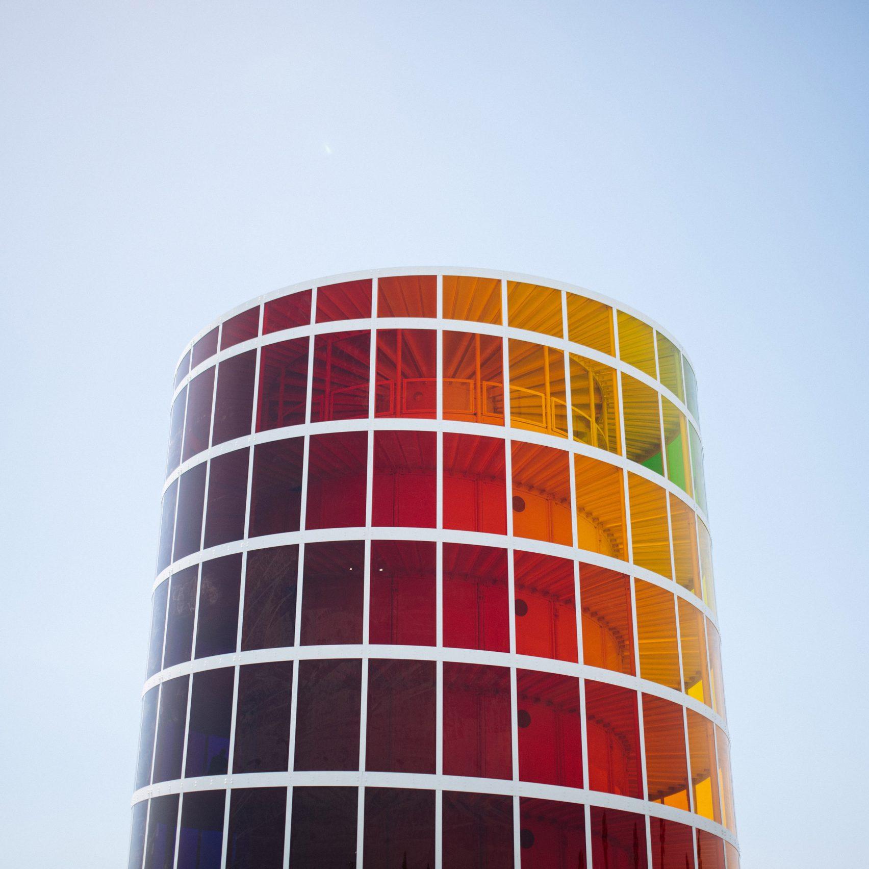 Oszklona wieża w kolorach tęczy na tle nieba.