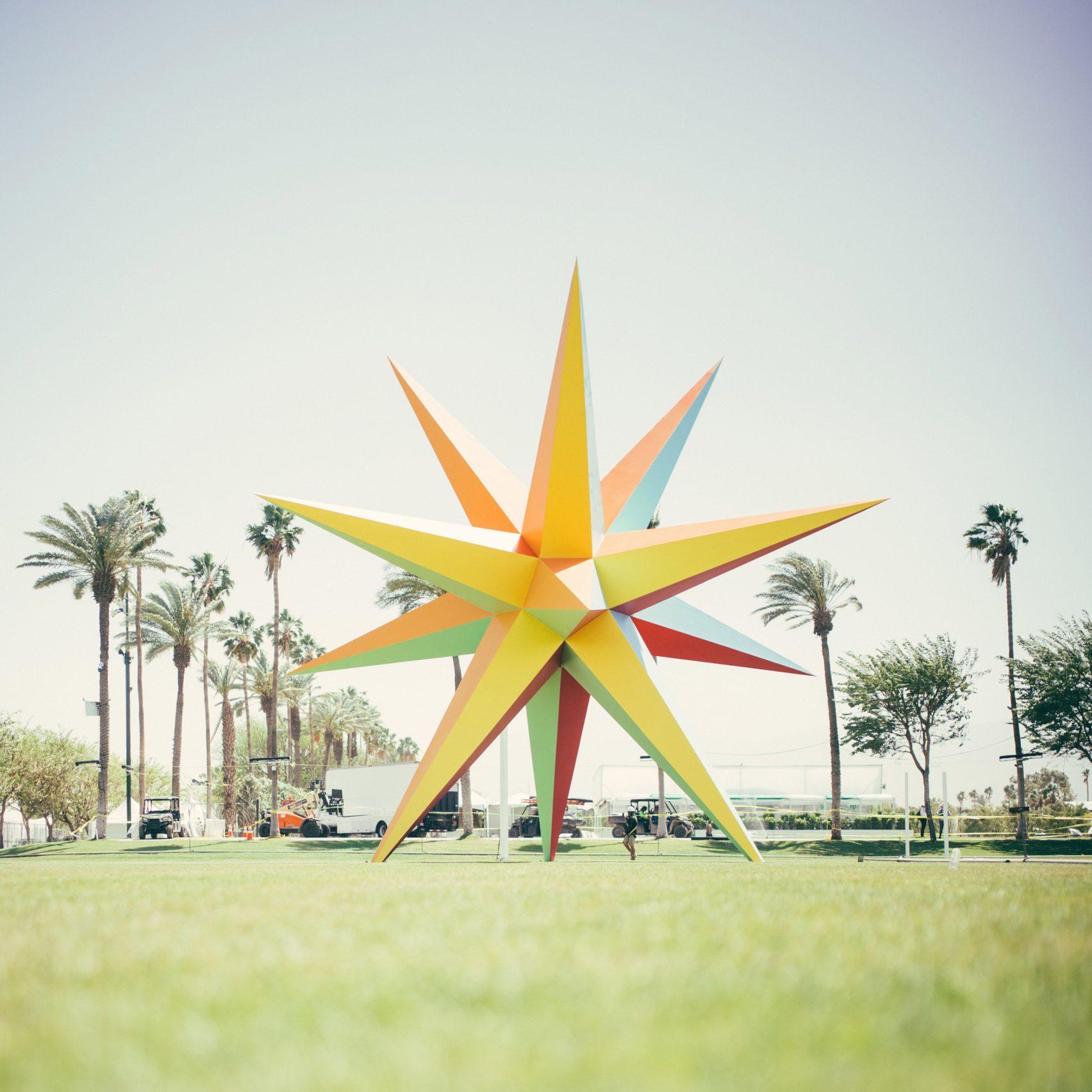 Wielokolorowa gwiazda na trawie, w tle palmy.