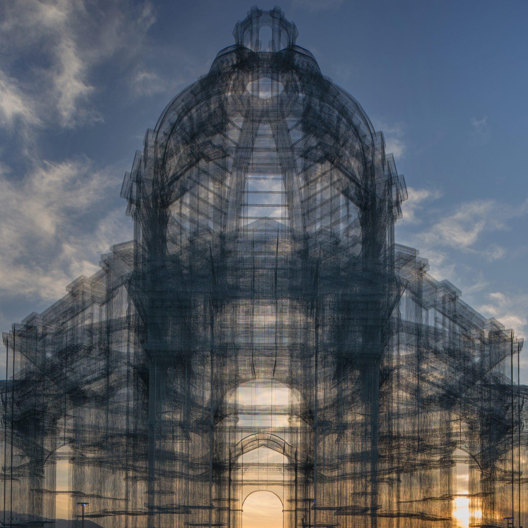 Siatka druciana uformowana w budowlę kościelną na tle nieba.
