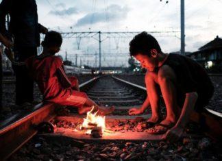 Na zdjeciu widac dzieci bawiace sie na torach i rozpalajace ogień