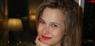 Uśmiechnięta dziewczyna trzymająca rękę pod brodą ubrana w szlafrok