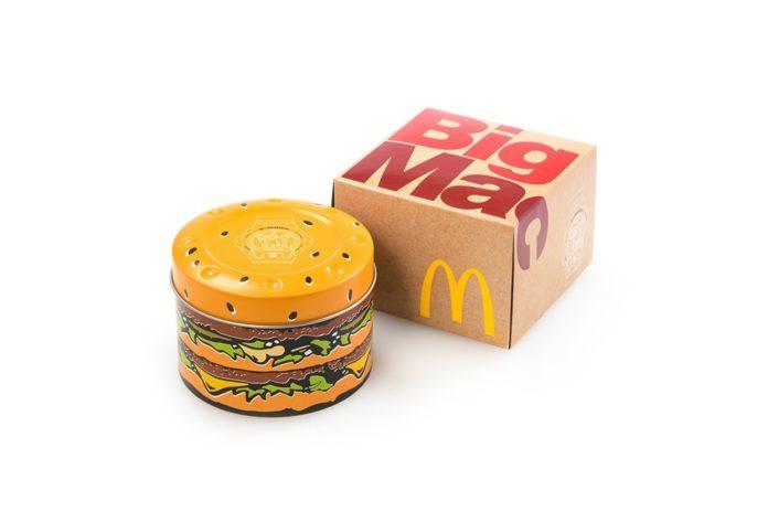 Papierowe pudełko z napisem Big Mac i puszka w kształcie hamburgera na białym tle.