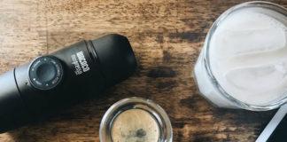 Przenośny ekspres do kawy leżący na stole, obok szklanka z espresso, szklanka z mlekiem i telefon