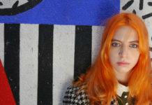 Rudowłosa dziewczyna na tle kolorowej ściany w paski