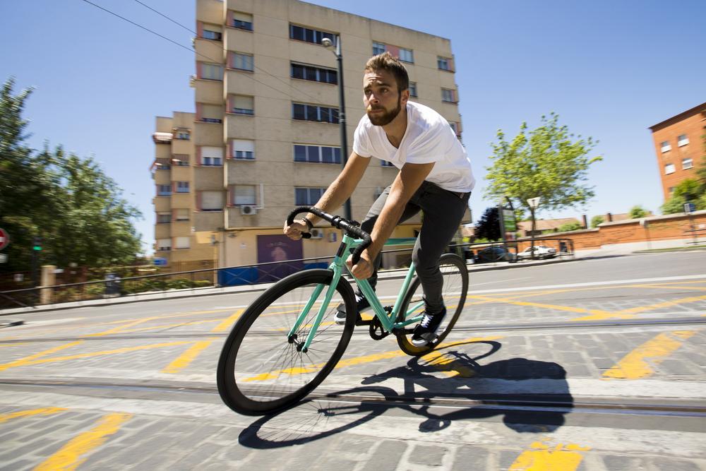 Mężczyzna jadący na rowerze ostrokołowym, w tle bloki