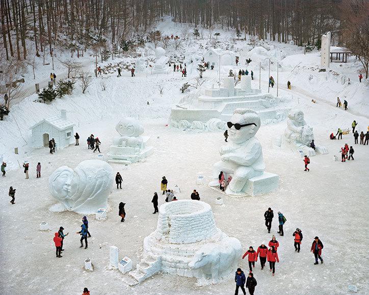 Zimowy park rozrywki z rzeźbami ze śniegu i ludzie dookoła