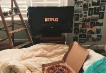Mały pokój, na łóżku pudełko z pizzą, zdjęcia przyklejone na ścianie, na ekranie napis Netflix.