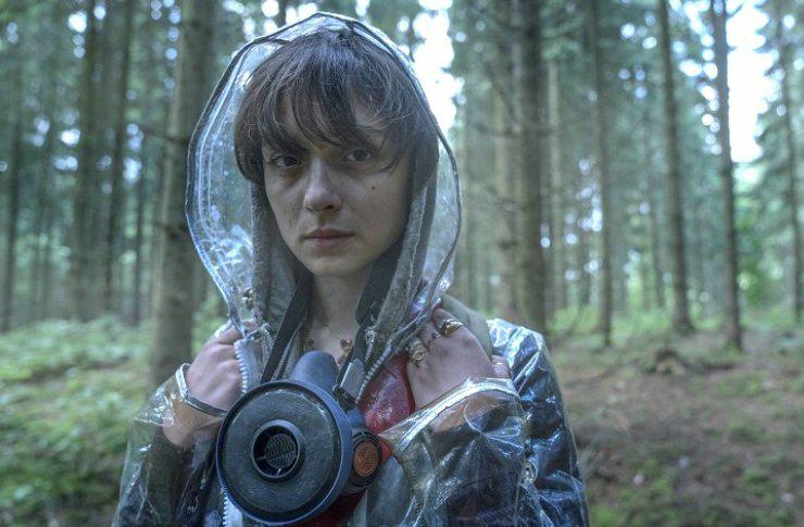 Dziewczyna ubrana w płaszcz przeciwdeszczowy z maską na szyi