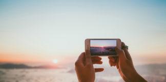 Dłonie trzymające telefon komórkowy, który robi zdjęcie zachodowi słońca nad morzem.