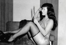 Czarno-białe zdjęcie kobiety siedzącej na kanapie w ponczochach