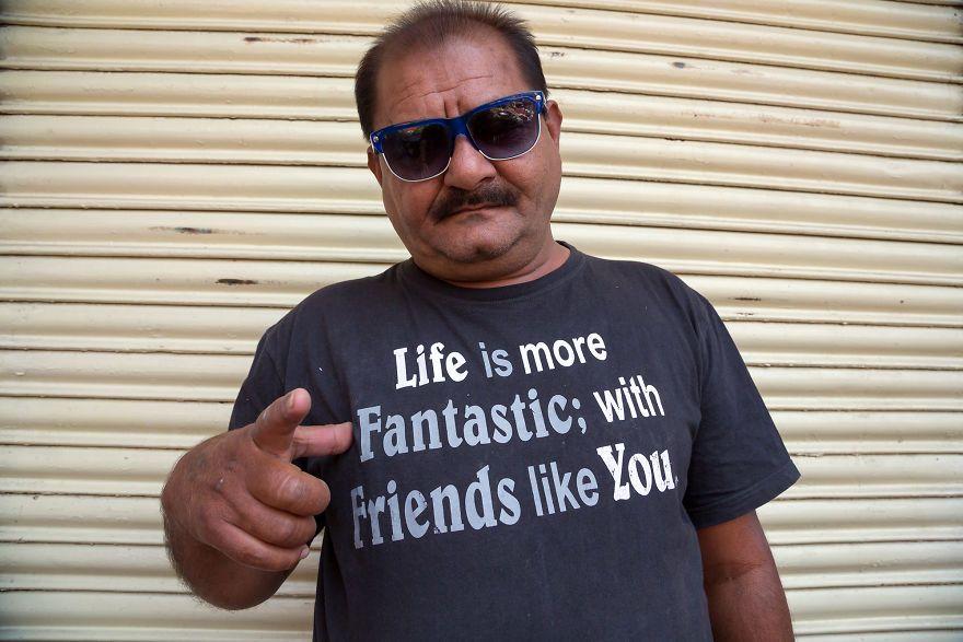 Mężczyzna w okualarch ubrany w koszulke z napisem