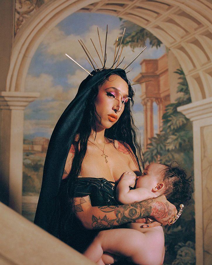 Kobieta w czarnej sukience z dzieckiem przy piersi