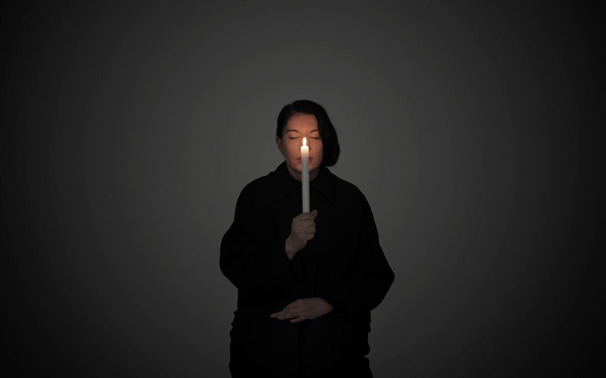 Kobieta w ciemnym stroju na ciemnym tle ze świecą w dłonii.