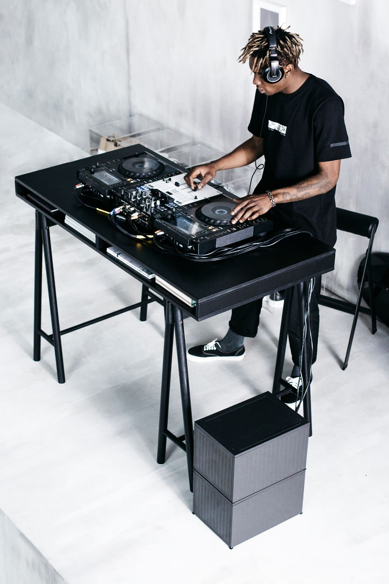 Mężczyzna w czarnym ubraniu grający jako DJ. Konsola na czarnym biurku.