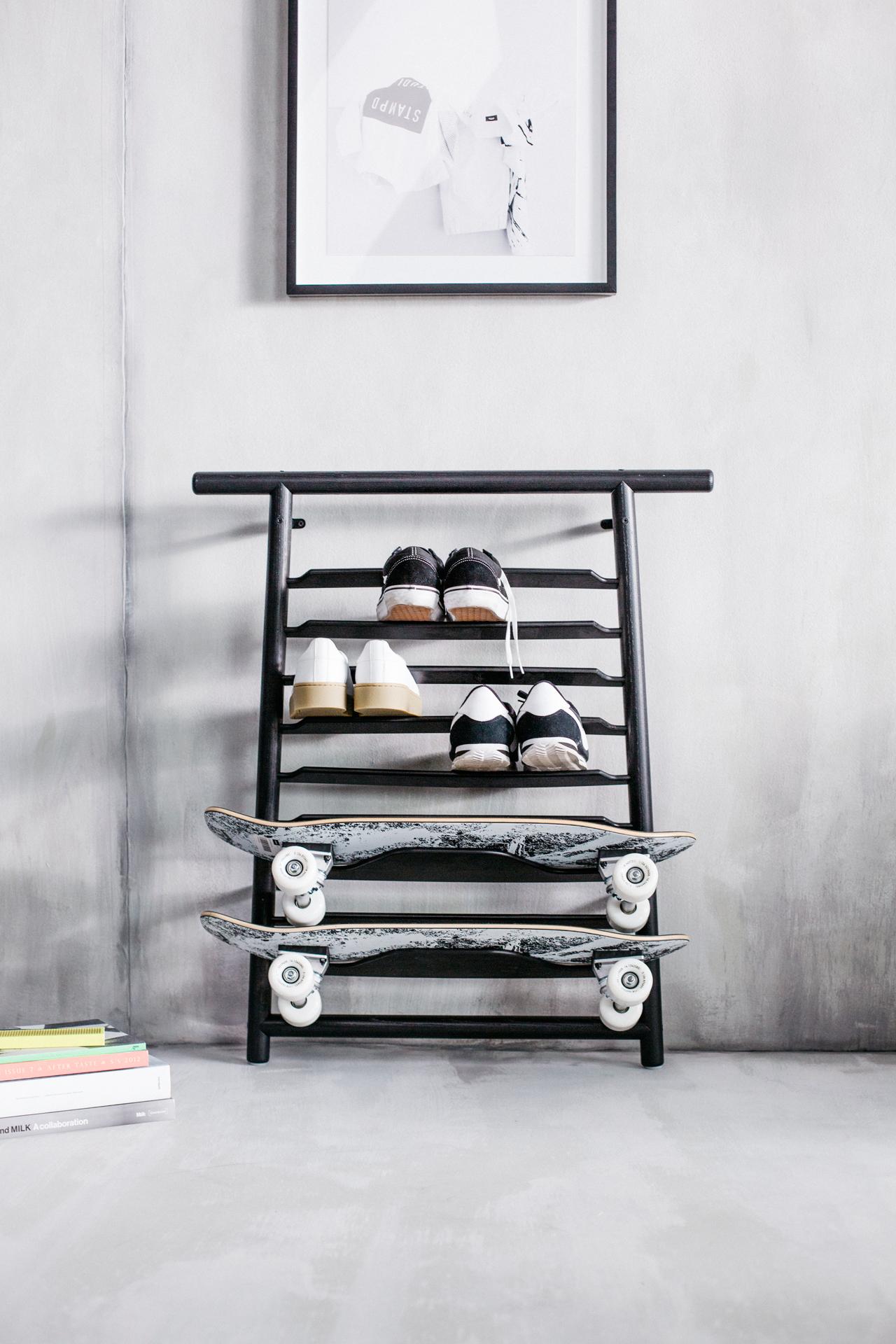 Czarna półka z butami i deskorolkami w betonowym wnętrzu.