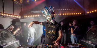 Mężczyzna przy konsolecie DJskiej w masce na twarzy